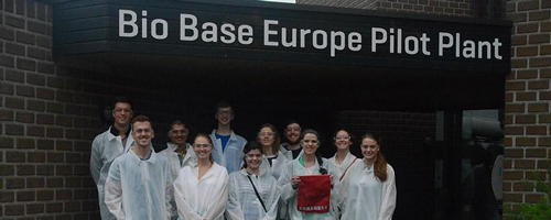 Student group posing for a photo in front of a European food science lab.