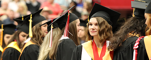 Honors student facing and smiling at the crowd at the 2019 Bumpers College Spring Commencement Ceremony.