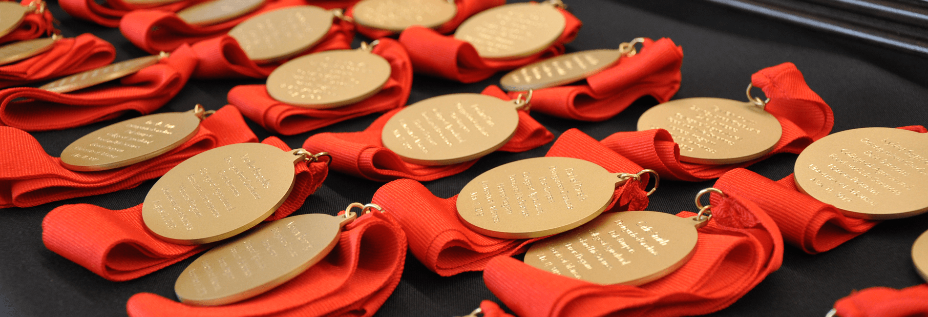 Gold medals with red ribbons lined up on a table for the 2019 Honors and Awards Banquet.