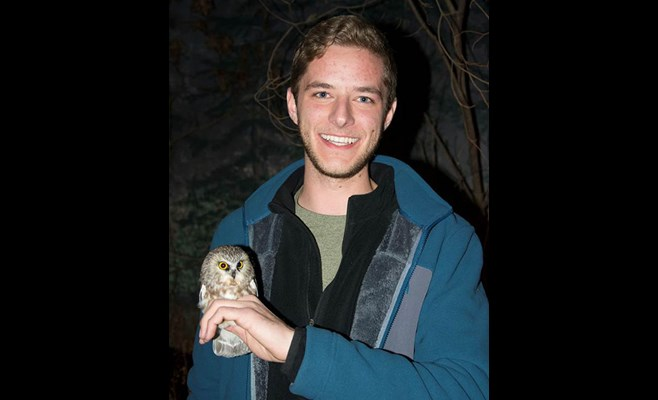 Mitchell Pruitt holding a baby saw whet owl.